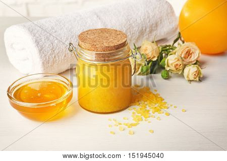 Spa concept. Natural facial mask with honey, towel and flowers on white table