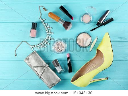 Flat lay of women cosmetics and accessories on blue wooden background