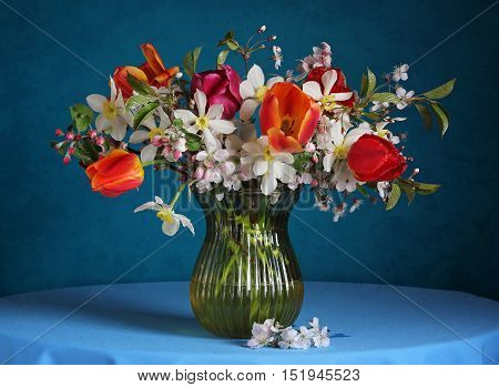 Still life with spring flowers on a blue background. Bouquet with daffodils tulips and branches of the cherry blossoms.