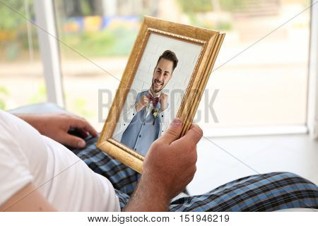 Male hands holding photo frame with picture of young man. Happy memories concept.
