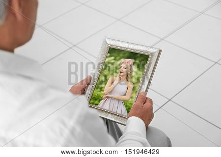 Male hands holding photo frame with picture of young woman. Happy memories concept.
