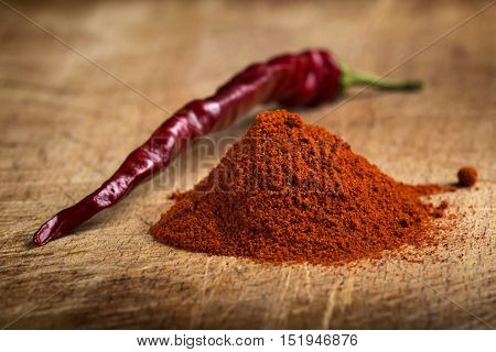 Red hot paprika powder heap and one dried chilli on wooden background