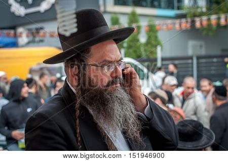 Elderly Hasid in traditional Jewish hat talking on the phone. Uman, Ukraine - 2 October 2016.