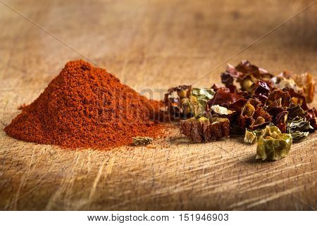 Red hot paprika powder and pieces of dried chiles on wooden background