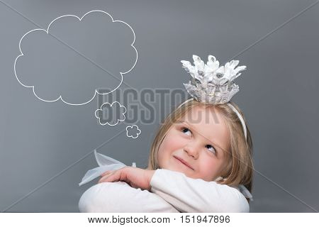 Little girl wearing a crown on a gray background dreaming looking up. Above it is a cloud of thoughts