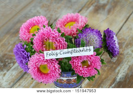 Feliz cumpleanos (which means happy birthday in Spanish) card with colorful daisy flower bouquet