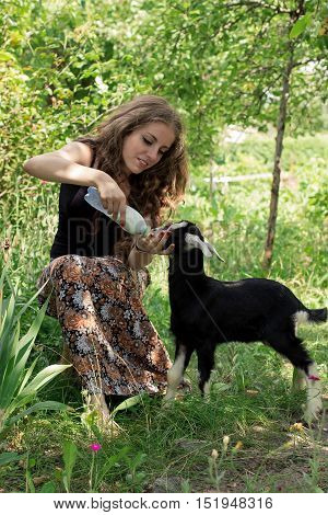 Attractive young woman is feeding a baby goat with milk from the bottle. Vertical orientation.