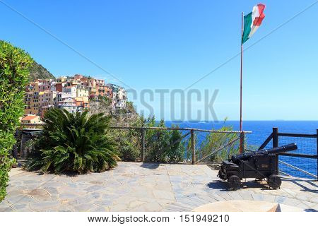 Old Cannon, Italian Flag And Cinque Terre Village Manarola With Colorful Houses And Mediterranean Se
