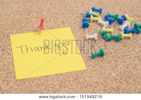 Hand writing - Thank you - words on yellow sticky note with colorful pins