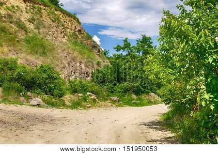 Dirt road in the Tokaj wine region in Hungary. Hungarian countryside. Cloudy blue sky. Trees and rocks. Junction. Summer season landscape.