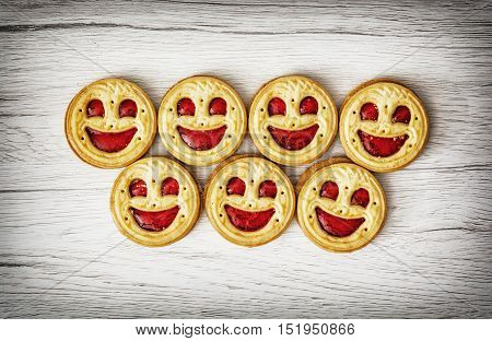 Seven round biscuits smiling faces. Tasty cookies. Humorous food. Jam biscuits. Food theme.