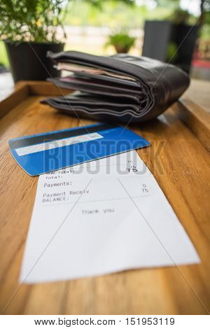 Receipt and credit card with wallet on wooden tray.