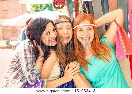 Playful hippies girls having fun together at flea market smiling at camera - Cheerful girlfriends shopping on street posing photo - Concept of women joyful moment in summer holiday - Warm filter tones