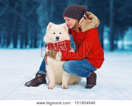 Christmas winter and people concept - happy young woman owner petting embracing white Samoyed dog on snow