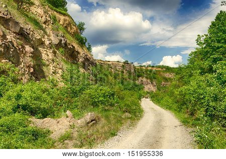 Dirt road in the Tokaj wine region in Hungary. Hungarian countryside. Cloudy blue sky.   Warm dry calm weather. Summer season landscape.