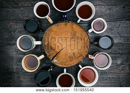 Wood slice in the middle of the circle of various tea cups and mugs. Flat lay