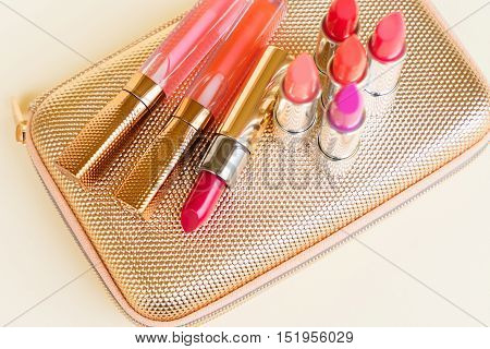 Collection of colorful lipsticks on golden woman pursue bag close up