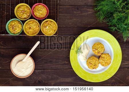 Muffins from cabbage with ham and cheese. Sour cream sauce. The top view