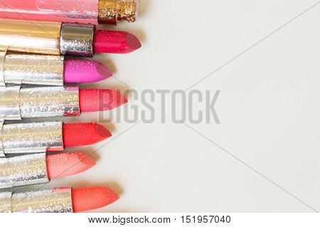 Set of wet lipsticks with copy space on beige background close up