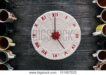 Knitted white and red clock with needle arrows reading five in the middle of various tea cups and mugs. Flat lay