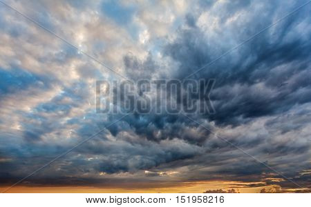 Beautiful dramatic sky with gray clouds and sunset. Dark blue feather shaped clouds in the background of bright orange sunset.