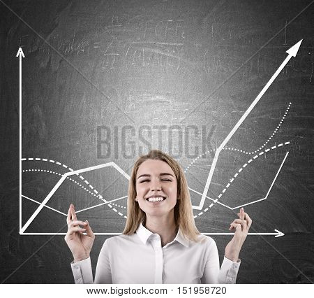 Woman with crossed fingers is standing near blackboard with growing graphs and dreaming for the trend to go on. Mock up