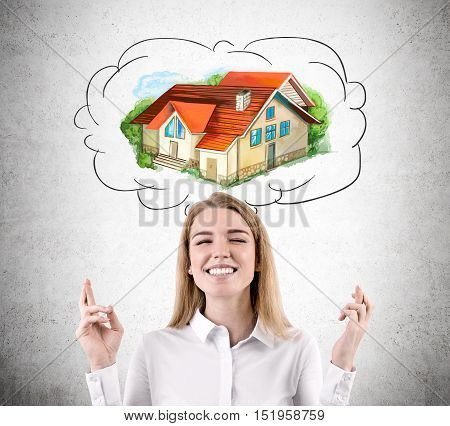Woman with crossed fingers is dreaming about new accommodation while standing against concrete wall. Concept of real estate market