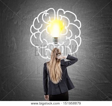 Woman scratching head looking at blackboard with light bulb and brain sketches. Concept of looking for solution