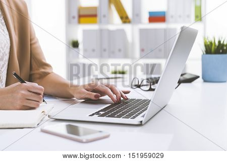 Close Up Of Girl In Beige Cardigan Writing And Typing