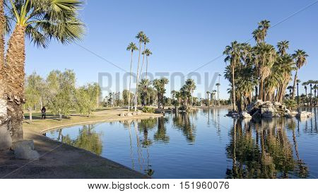 Bright and clear winter sky reflecting in deep blue water of Encanto park lake Phoenix downtown Arizona; Copyspace