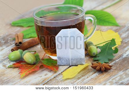Tea bag leaning against glass with black tea, and autumn leaves