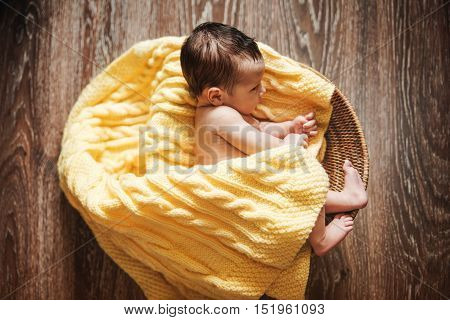 Newborn Baby Girl is in the Rattan Basket with Knitted Rug.