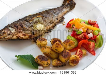 Roasted trout on white plate with lemon and roasted potatoes.