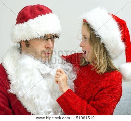 Surprised Little Girl Looking At Fake Santa Claus.
