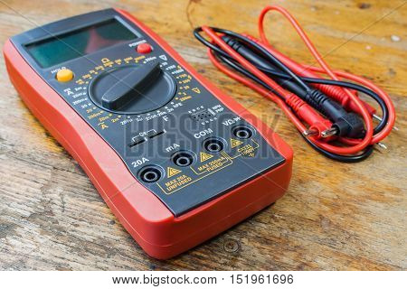 Digital multimeter and set of probes on a table in a workshop
