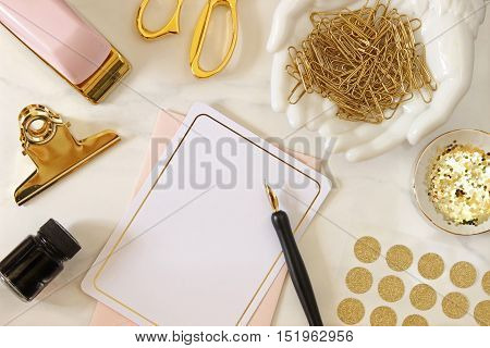 Over head flat lay desktop with pink and gold office supplies with stationary and pen and ink