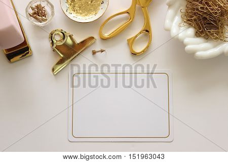 Over head flat lay desktop with pink and gold office supplies and blank notecard