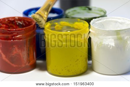 paint different colors black red white green yellow blue in open jars gouache brush drawing creativity