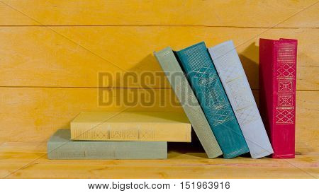 Stack of old books on wooden background
