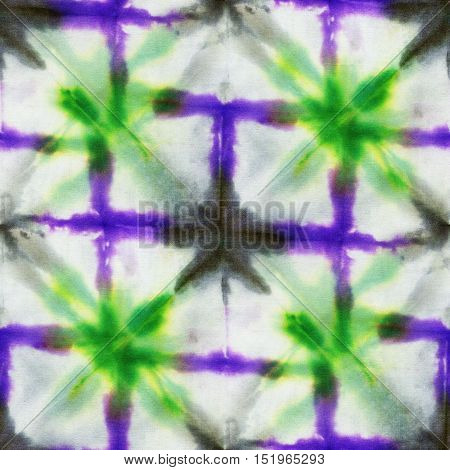 Seamless tie-dye pattern with a green and purple geometrical ornament. Hand painting fabrics - nodular batik. Shibori dyeing.