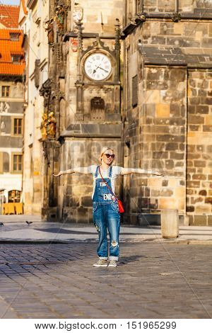 Young female traveler standing with wide open arms at the Old Town Square in Prague against the backdrop of the Old Town Hall, Czech Republic.