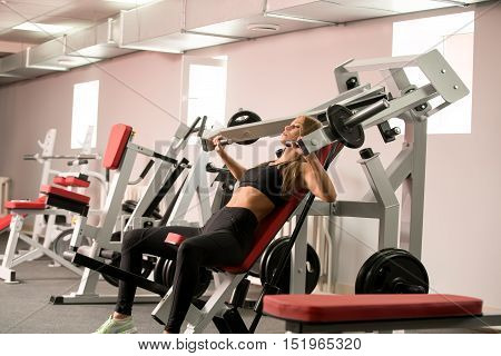 At gym. Image of sporty woman exercising on simulator