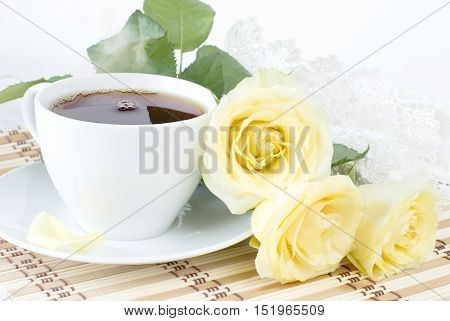 cup of morning tea a bouquet of yellow roses and vintage lacy doily on white background