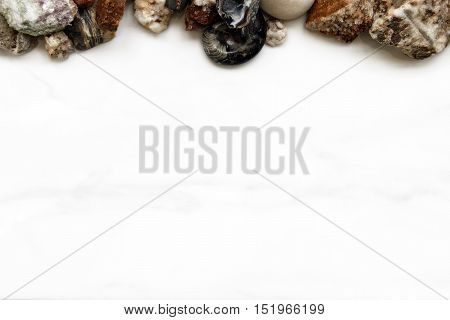 Rocks and fossils frame marble white background