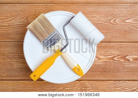 Bank of paint, paint brush and paint roller on a wooden background