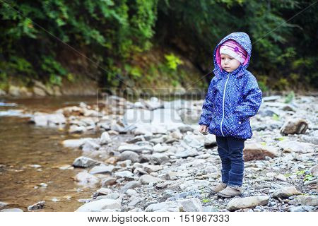 little girl stands near the river. The concept of travel and childhood.