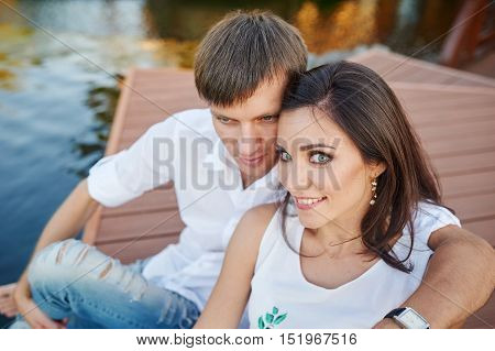 man embraces woman sitting on a pier at the river bank.