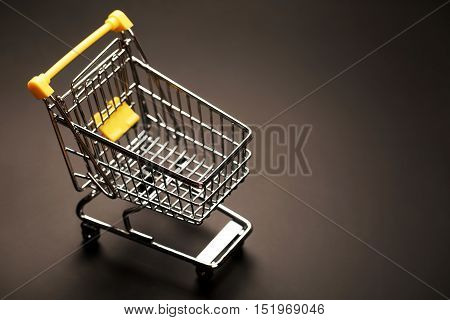 Metal shopping trolley at the supermarket on a black background