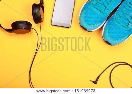 Black headphones, smart phone and blue sneakers on yellow  background. Concept of active lifestyle.
