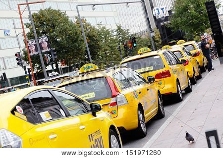 Stockholm, Sweden - September 25, 2016: A row of yellow taxi cabs parked at the taxi stand outside the Stockholm Central station.
